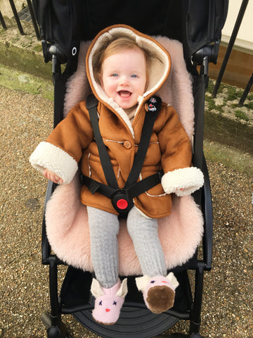 baby sat on rose Binibamba sheepskin pram liner looking all snugly in her pushchair