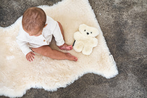 baby sat on sheepskin rug with binibear sheepskin teddy bear