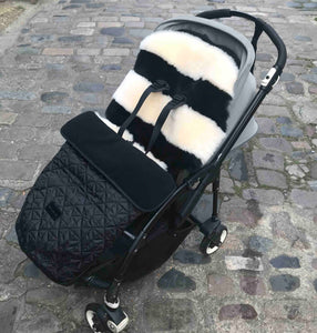 monochrome sheepskin stripe buggy liner shown in pushchair with footmuff