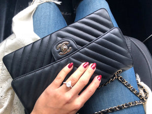 Woman Holding Chanel Black Chevron Medium Flap Bag