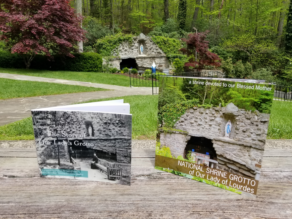 """The Story of Our Lady's Grotto"" book and ""NATIONAL SHRINE GROTTO of Our Lady of Lourdes"" book with cave grotto in background at National Shrine Grotto in Emmitsburg Maryland"