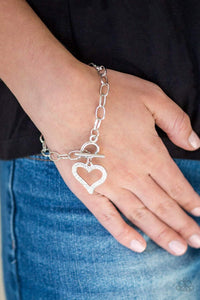 Paparazzi March To A Different HEARTBEAT - White Rhinestone Heart Charm Bracelet - Bling It On Online