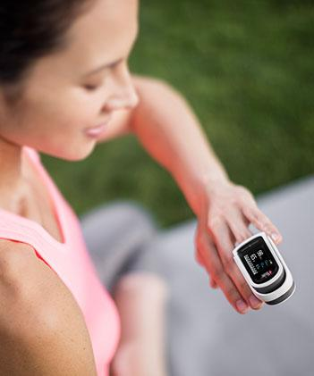 woman using fingertip pulse oximeter after workout