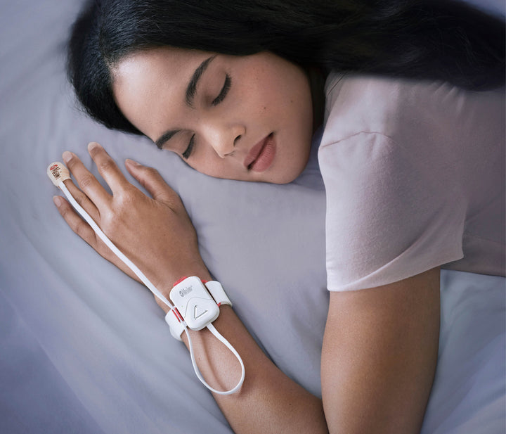 Woman sleeping on right side with Masimo Sleep sensor on left hand