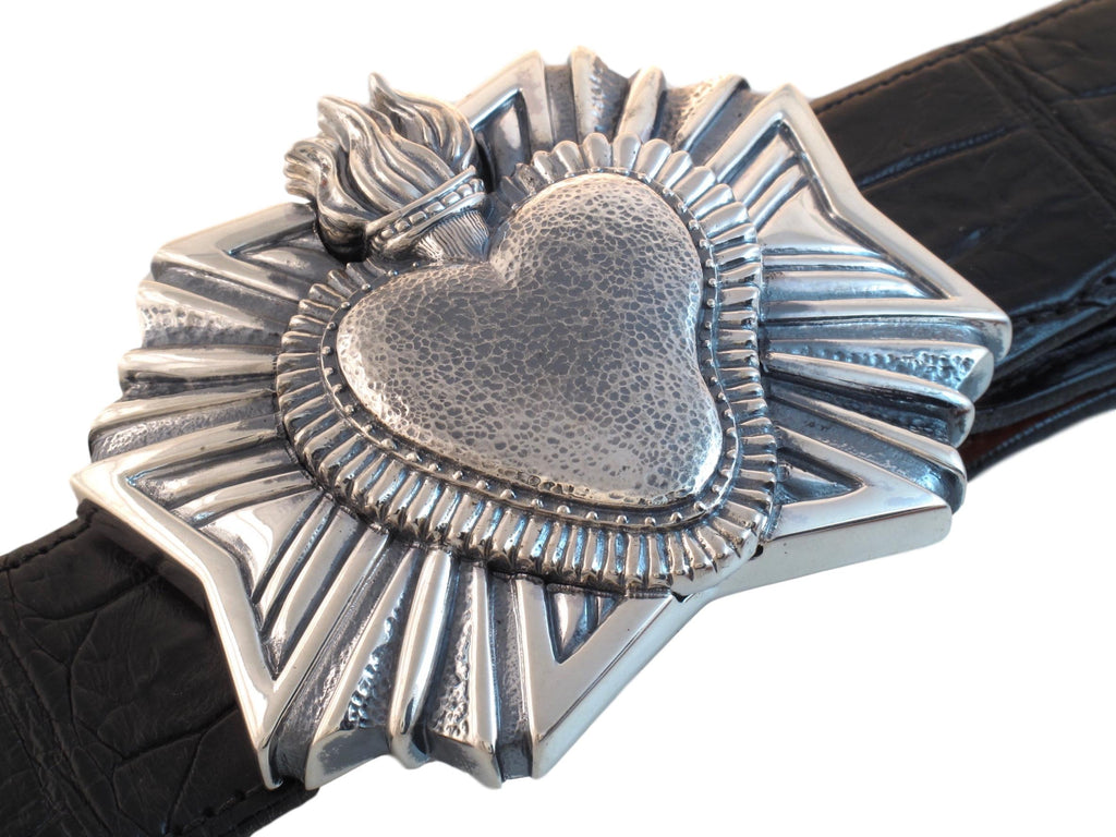 Angled view from above of the sterling Heart Milagro buckle on a black Alligator strap.