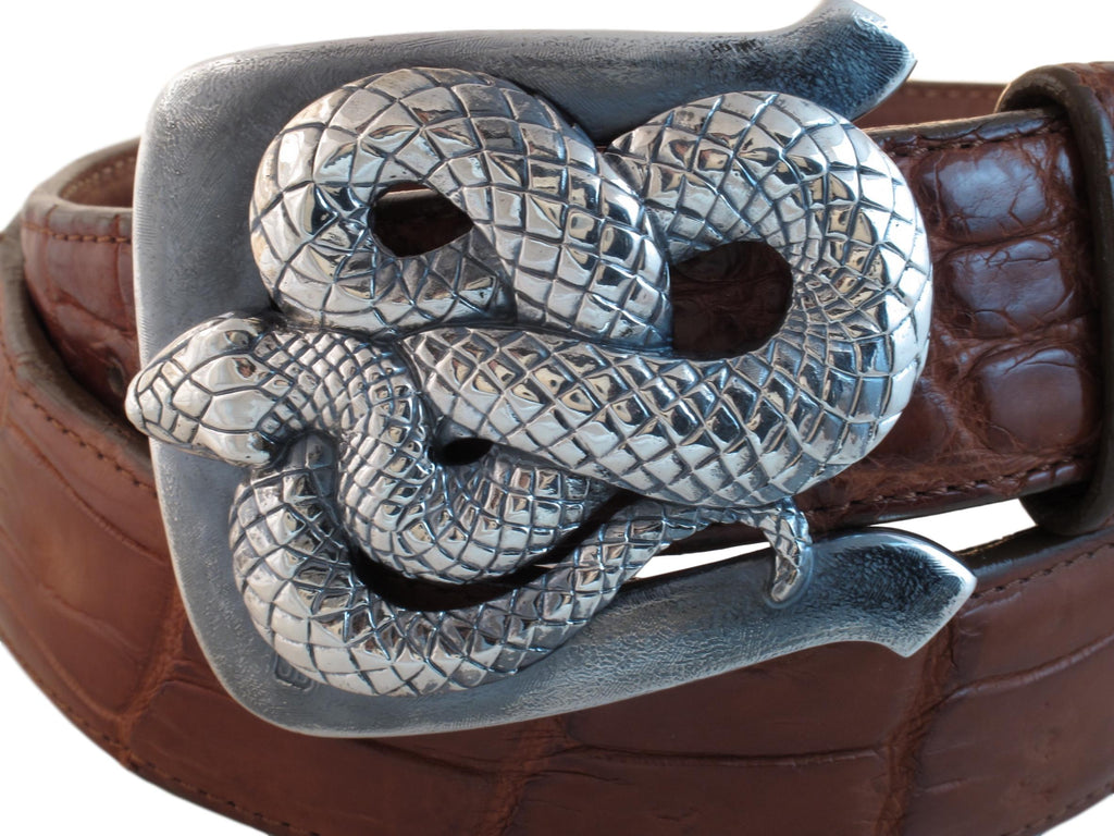 Coiled Snake buckle rests on a wrapped rust colored Alligator strap