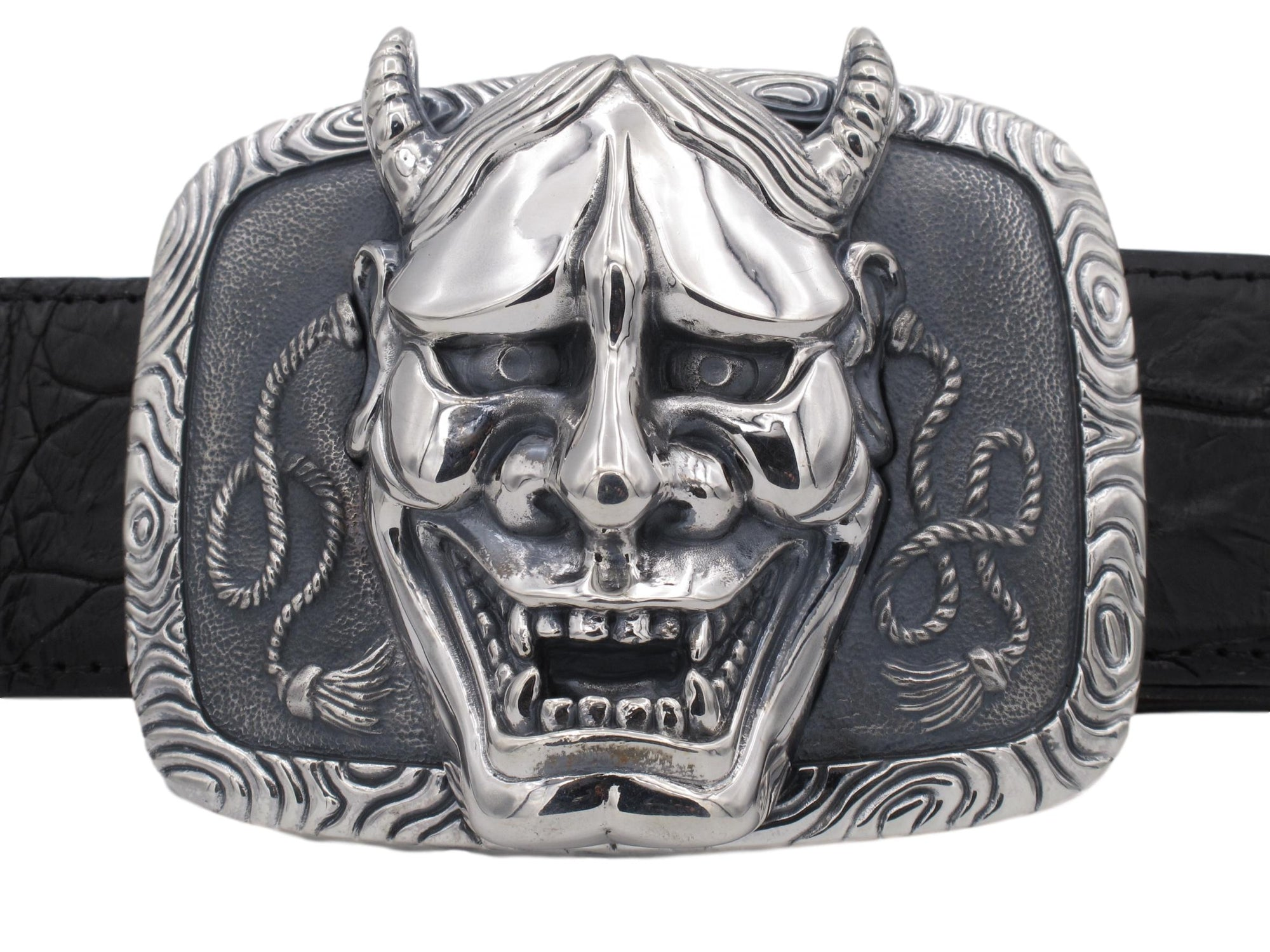 Front on view of the Sterling Hanya Mask Trophy buckle featuring the high relief sculpting of the mask set on a decorated and antiqued base.