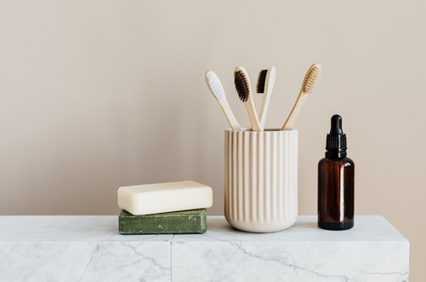 4 bamboo toothbrushes in stone clay toothbrush holder