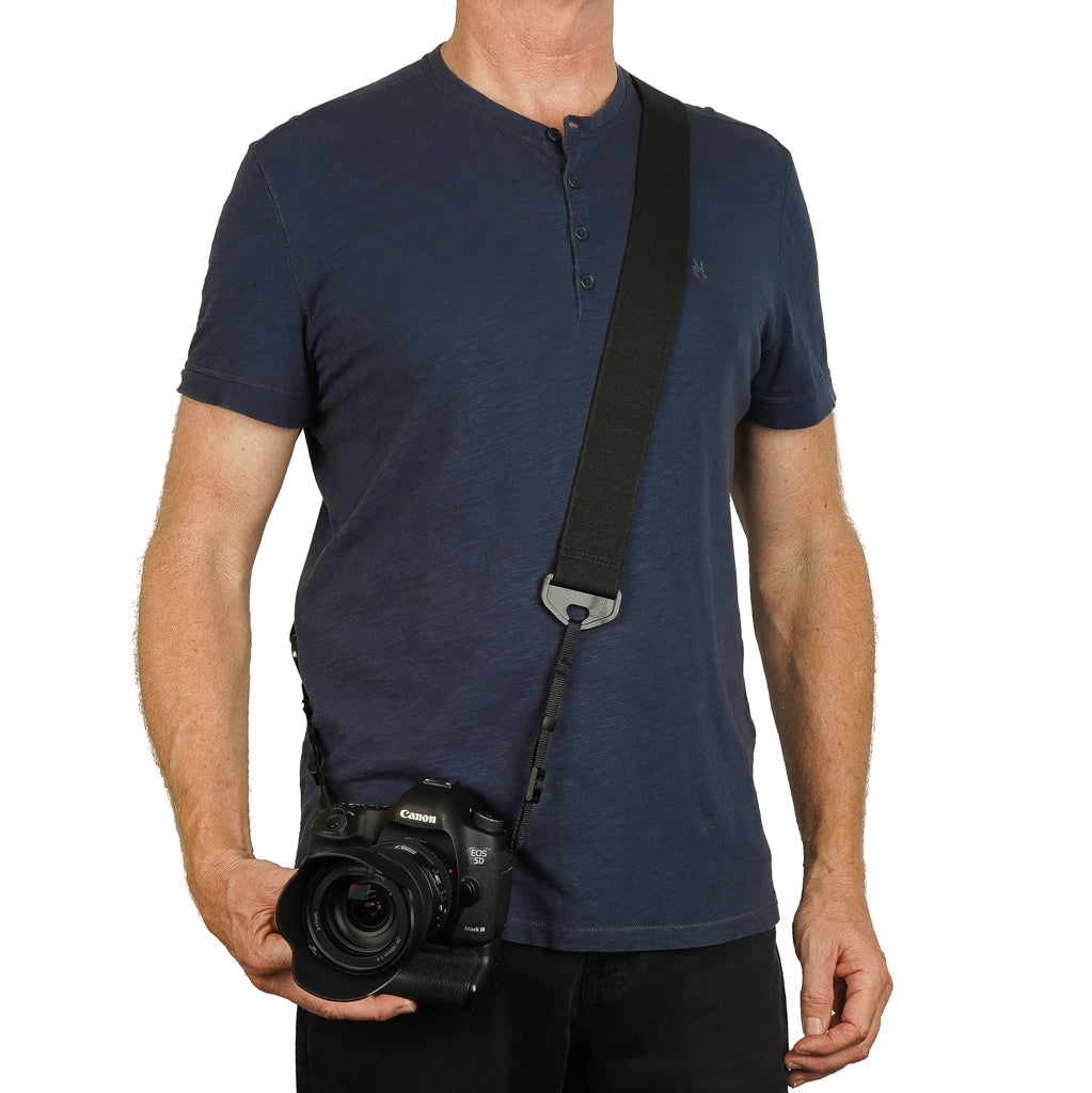 "Canon camera on a man with a camera strap made of 2"" wide heavy-duty elastic material over shoulder"
