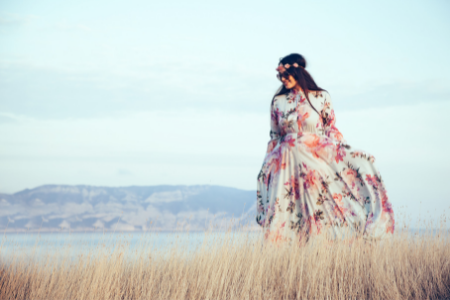 plus sized model in long floor length dress in long grass with mountains in the background