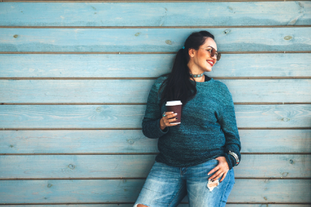 plus sized model holding coffee with sunglasses smiling in jeans and a blue jumper