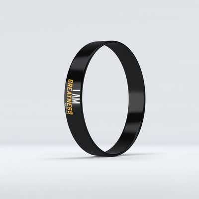 I AM Greatness wristband in black, white, and gold lettering.