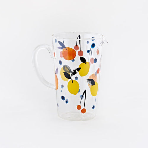 A glass pitcher decorated with lemons, cherries, blueberries, and oranges