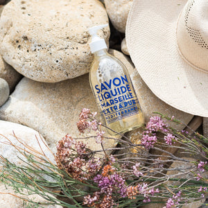 "Glass Liquid Soap bottle labeled ""Savon Liquide Marseille Extra pur, Mediterranee"" on top of rocks next to a sun hat and wildflowers."