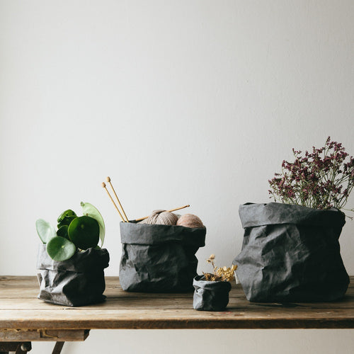 Four Dark Gray Uashmama Paper Bags in different sizes placed on a wood tabletop. Large Dark Gray bag holds lavender, Medium bag stores yarn and knitting needles. A small dark gray bag holds a house plant and a mini dark gray paper bag stores a small bunch of wheat.