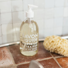 "Load image into Gallery viewer, Glass Liquid Soap bottle labeled ""Savon Liquide Marseille Extra pur, Fleur de Coton"" on terra cotta tiles in front of white square tile backsplash."