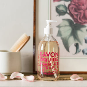 "Glass Liquid Soap bottle labeled ""Savon Liquide Marseille Extra pur, Rose Sauvage"" in front of rose art print and flower petals"