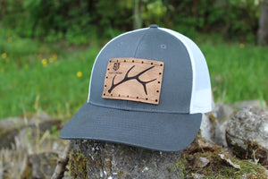Grey w/ white mesh custom trucker style hat with R&A Elk Shed Logo