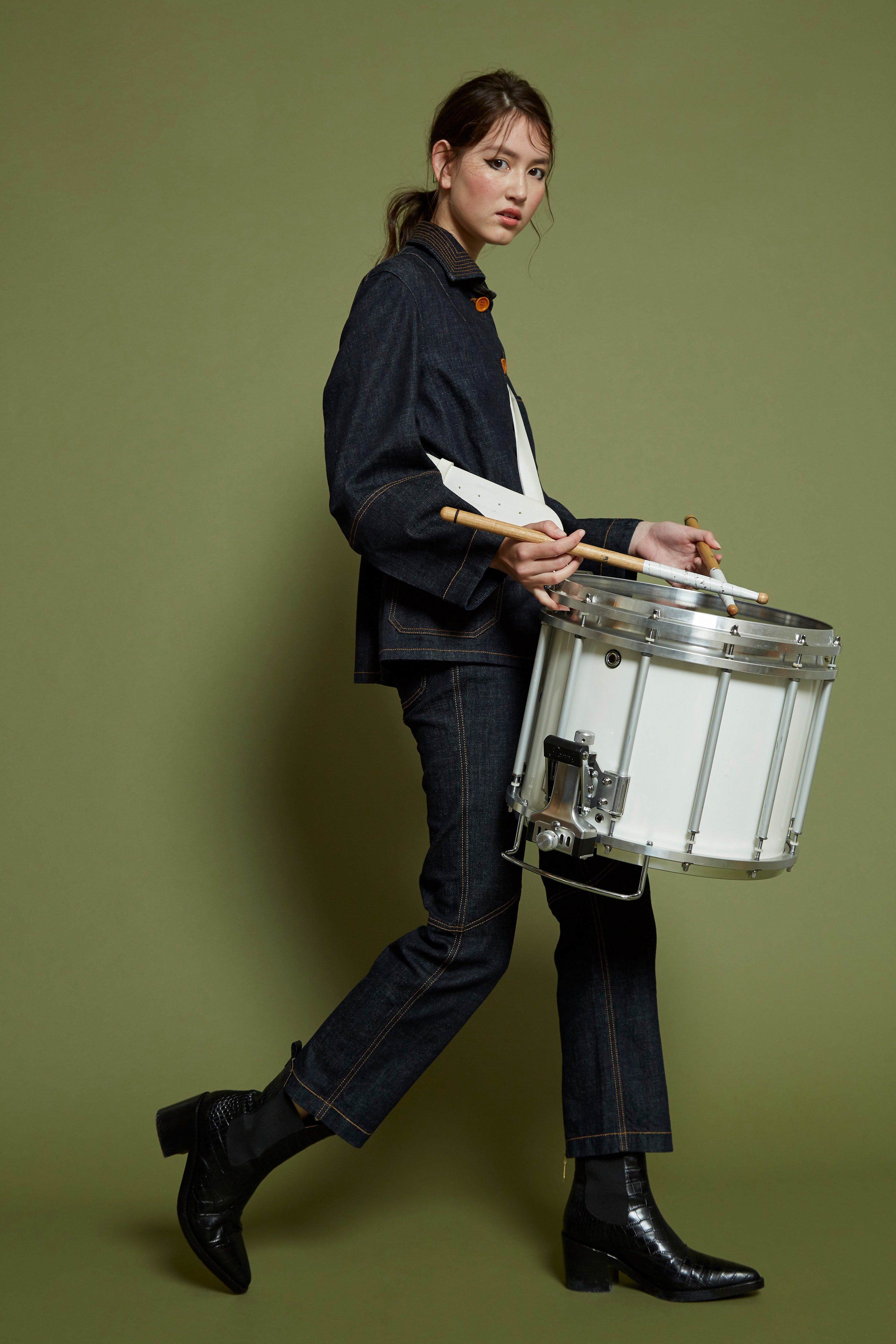 Woman playing drum wearing double denim from Outland Denim x Karen Walker collaboration