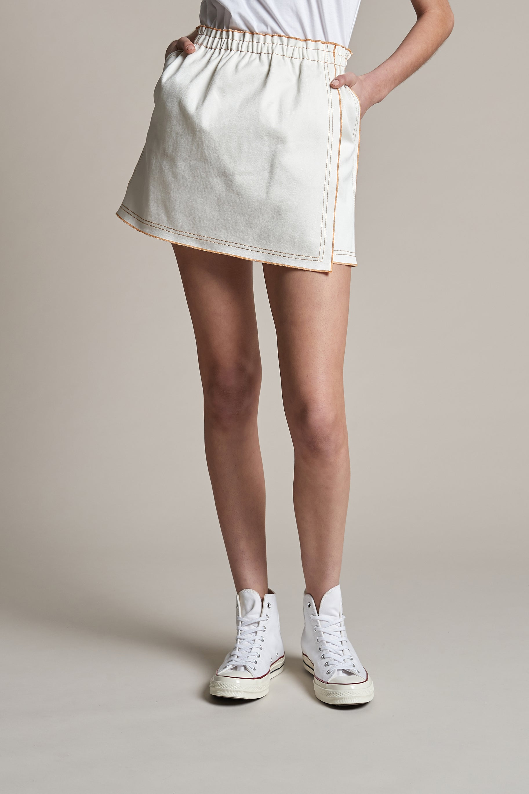 Woman wearing white denim mini skirt from outland denim x karen walker collaboration