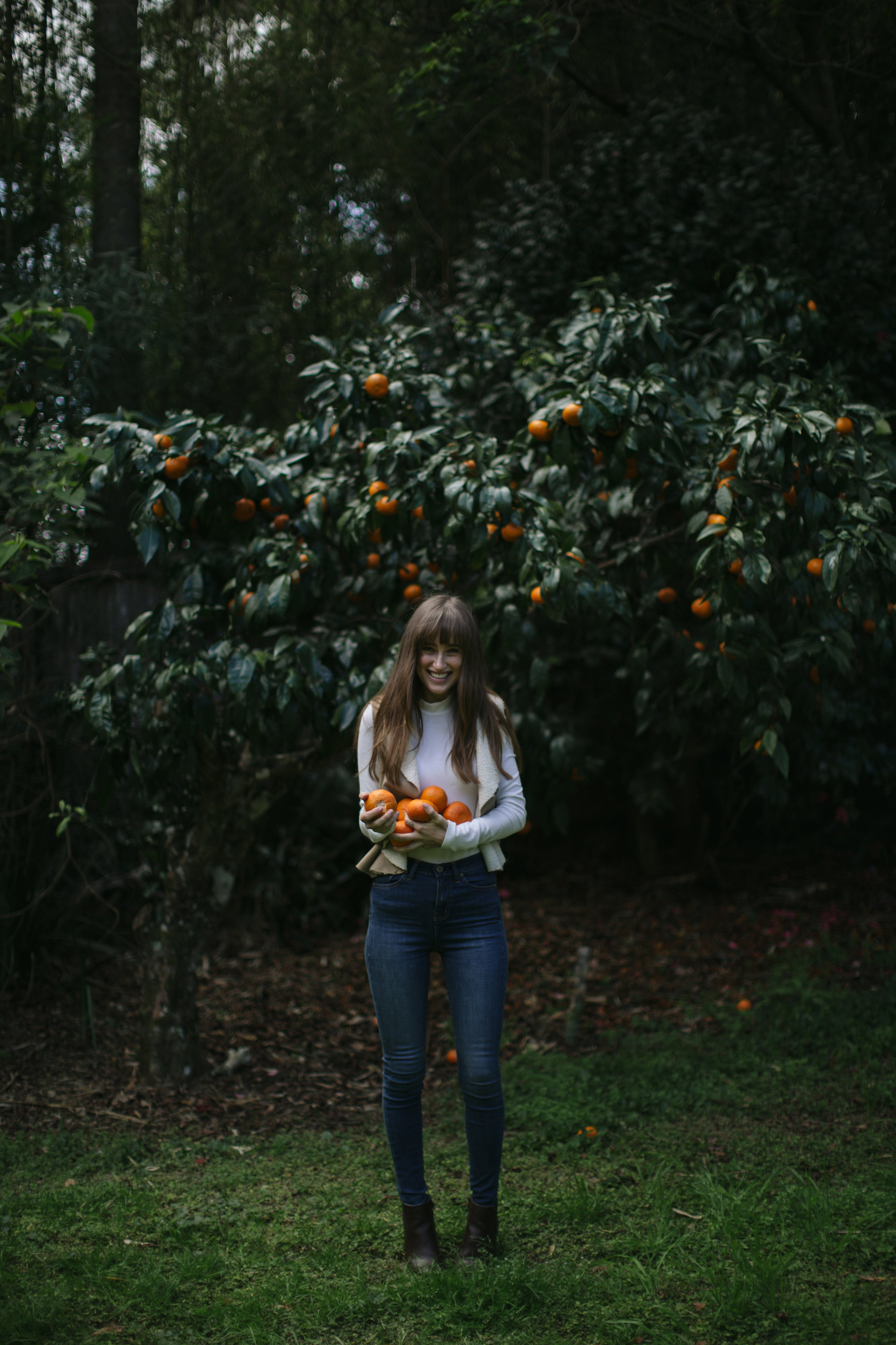 woman smiling picking oranges wearing outland denim jeans