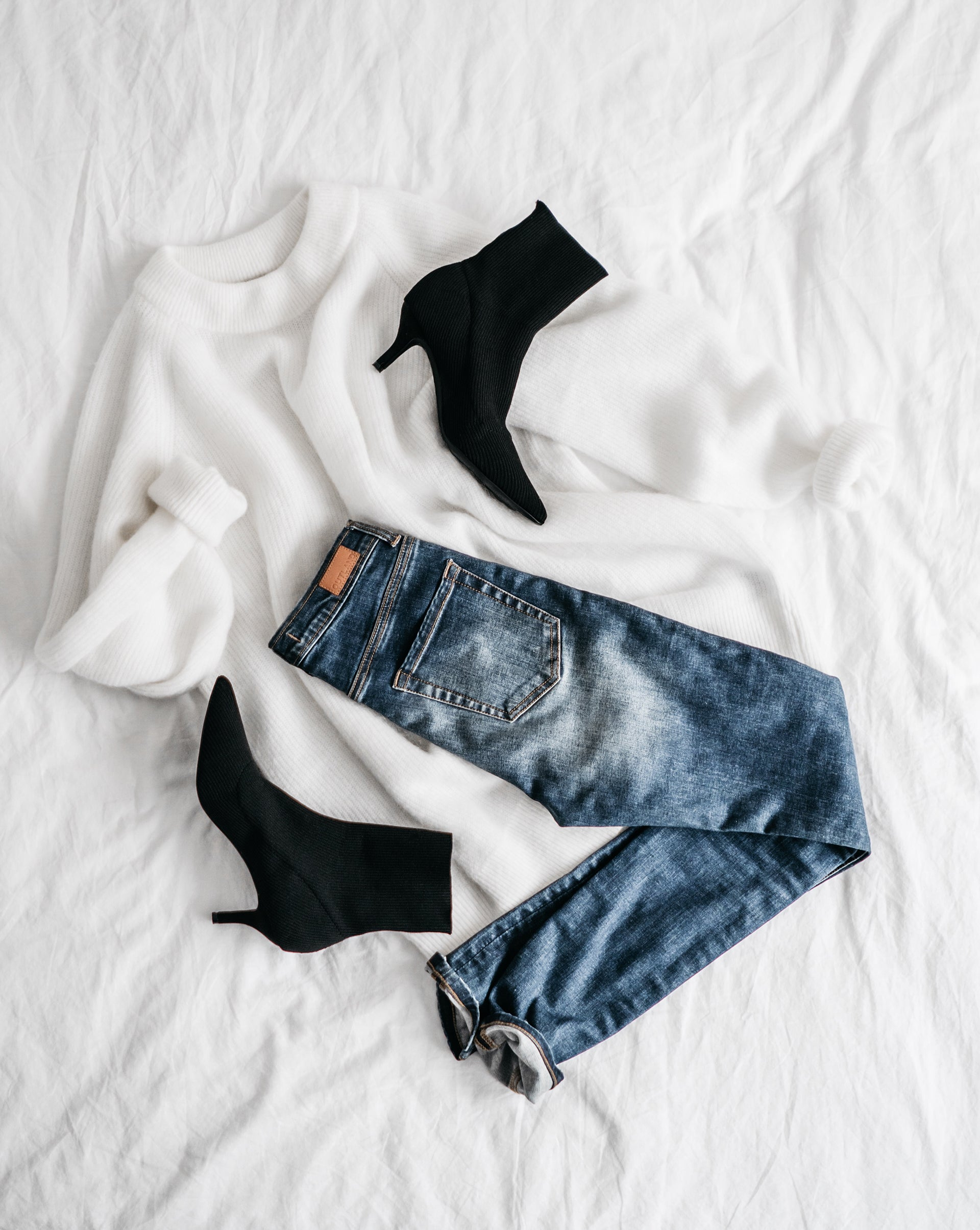 flatlay of jeans and sweaters