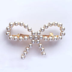 Bow shaped hair clip in gold with small pearls