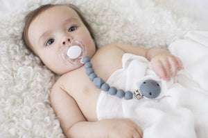 The Les Enfants Chewy Pacifier Clip grey with a baby model and white les enfants 100% bamboo muslin blanket