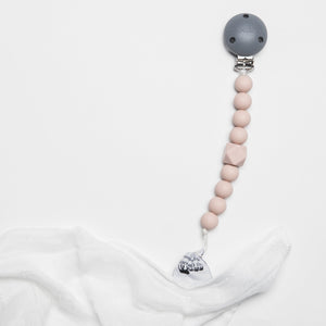 The Les Enfants Chewy Pacifier Clip pink attached to white security blanket