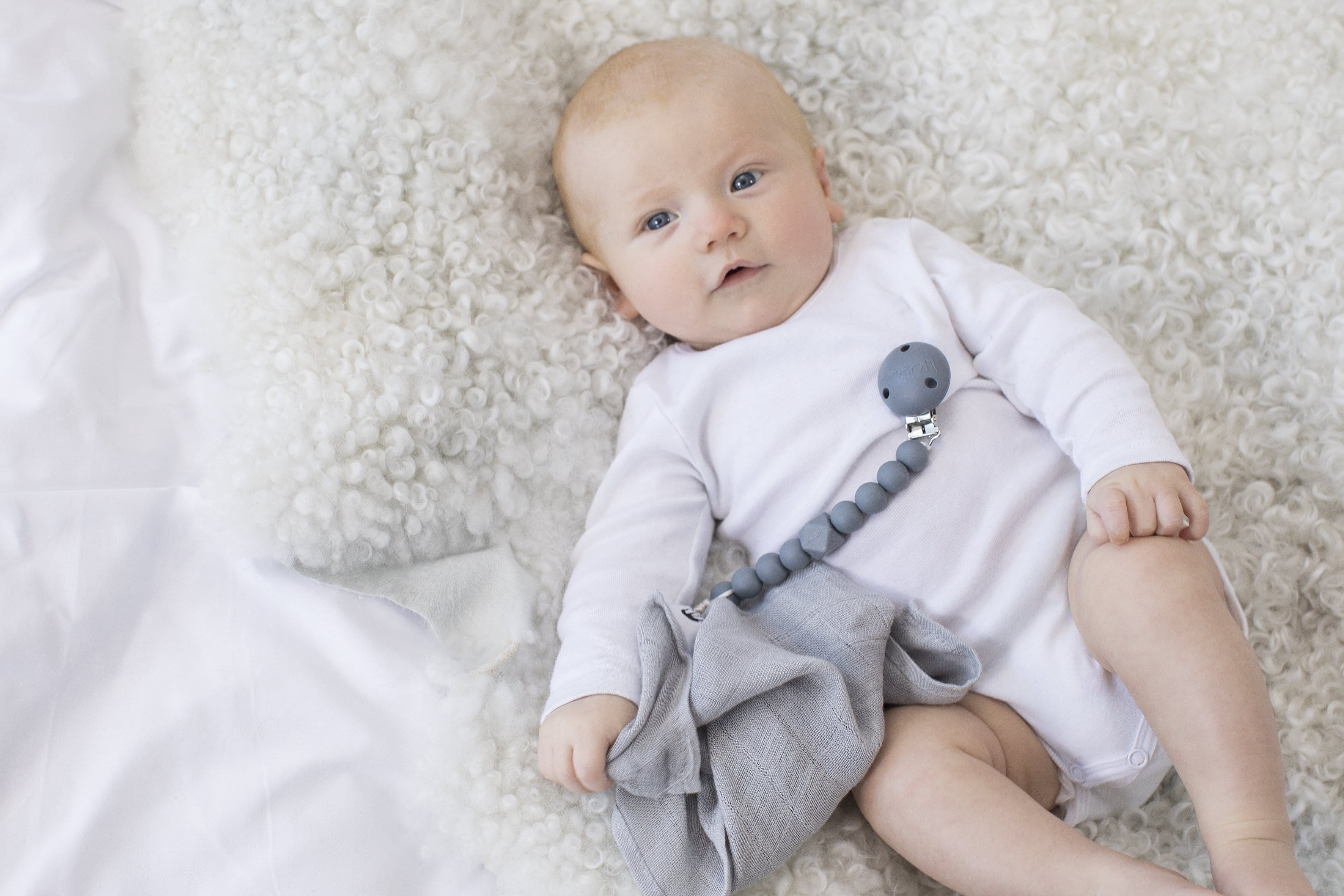 The Les Enfants Chewy Pacifier Clip grey with a blond baby model and grey les enfants 100% bamboo muslinblanket