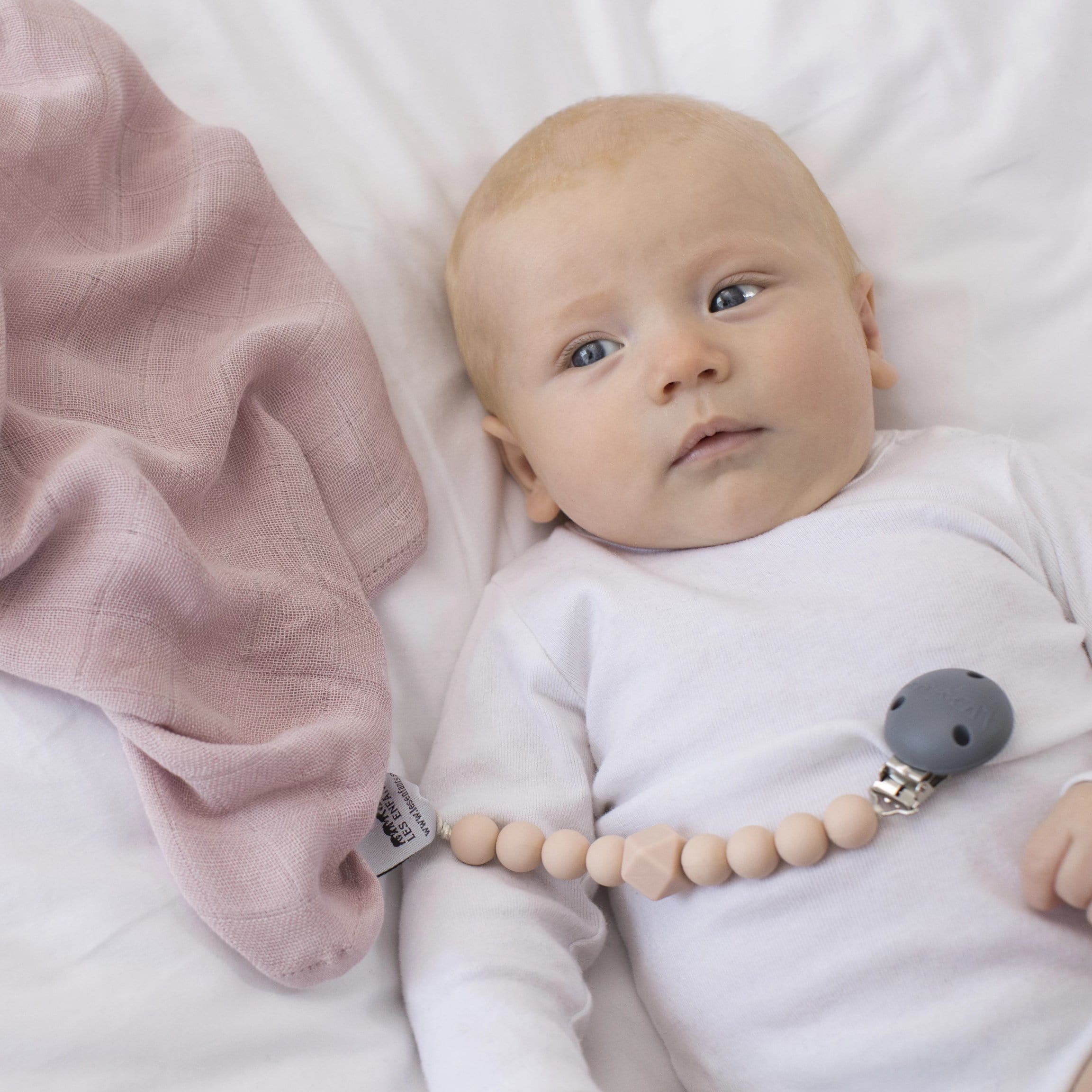 The Les Enfants Chewy Pacifier Clip pink with blond model and pink 100% bamboo muslin blanket