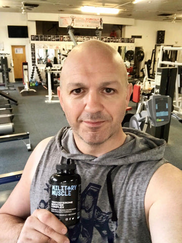 JOHN CUSTOMER HOLDING BOTTLE OF MILITARY MUSCLE IN GYM