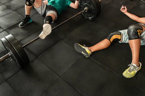 TWO PEOPLE LAYING ON THE GYM FLOOR WITH A BARBELL