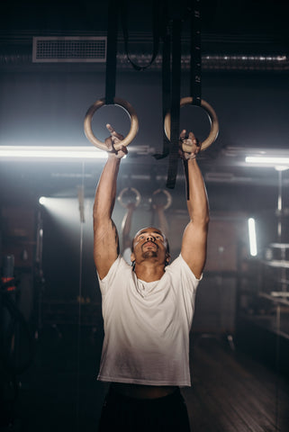 man using gymnastic rings for pull ups