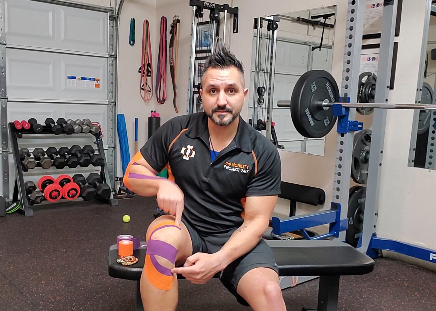 man_pointing_on_his_knee_with_kinesiology_tape