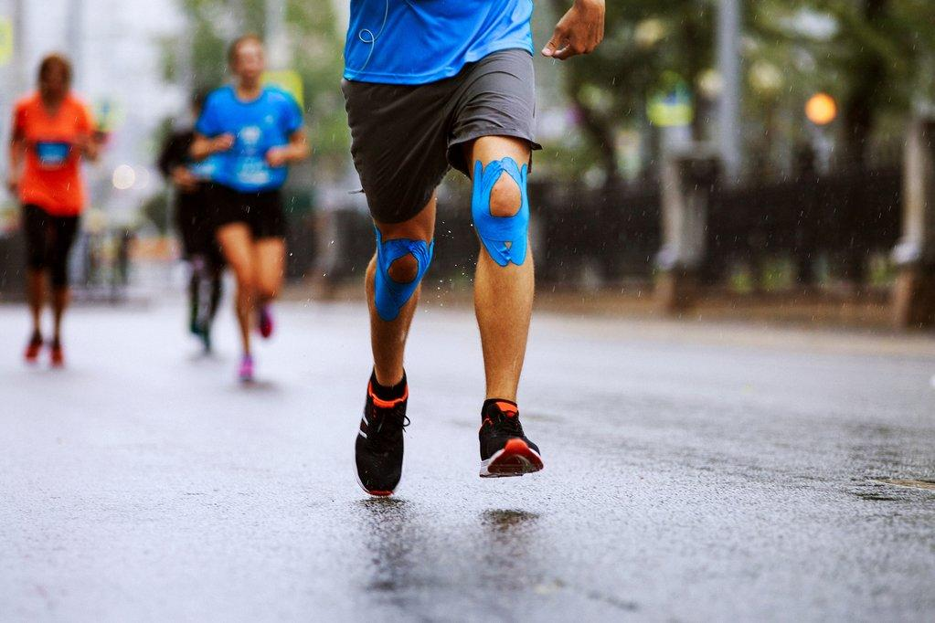 man running in a race with kinesiology tape
