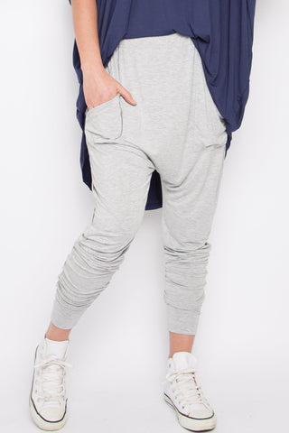 Model wears light grey bamboo viscose pants with a drop crotch