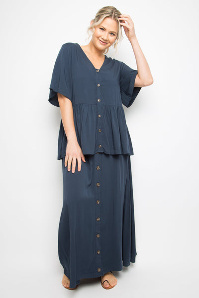 Model wears maxi length, navy blue skirt with tortoise button detail down the length of the front with matching top