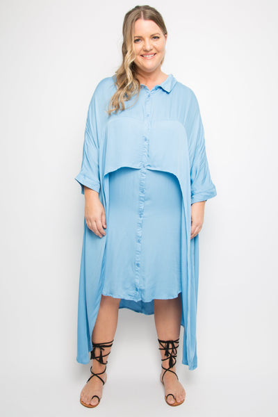 curve model wears sky blue button up shirt dress that has a cascading outer layer