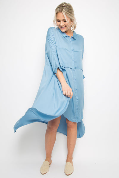 model wears sky blue button up shirt dress that has a cascading outer layer