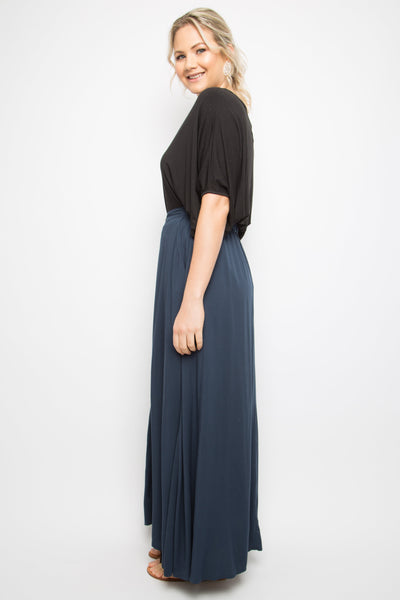 Model wears maxi length, navy blue skirt with tortoise button detail down the length of the front
