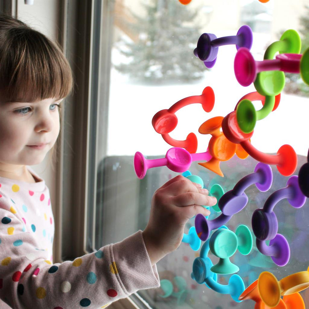 kind speelt met Fat Brain Toys Squigz 2.0