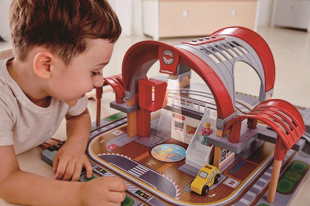 kind speelt met Hape Grand City station houten treinset