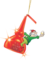 A Christmas elf swinging joyfully on a copper still and holding a wee dram
