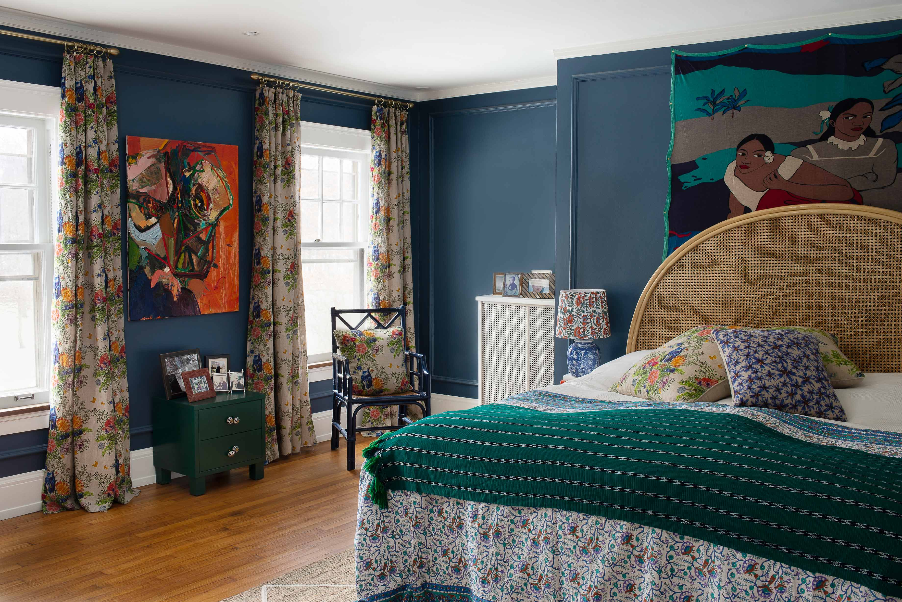 Blue painted bedroom with floral print linen curtains, colorful art and organic linen throwpillows on the bed.
