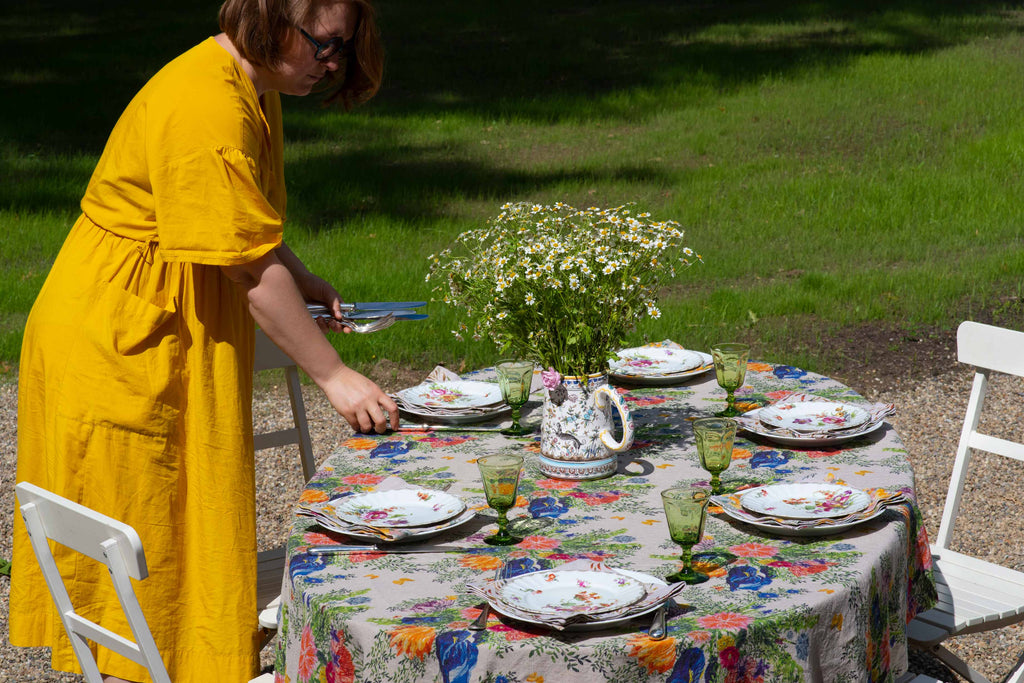 Sophie is setting the table with an organic linen tablecloth printed in floral patterns and colorful plates and glasses