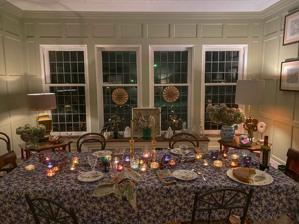 After dinner moody shot of dining room with candles lit and empty plates. Table is set with blue organic linen tablecloth and colorful organic linen napkins.