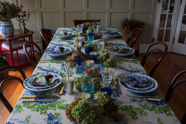 Beautiful table setting with organic linen green and blue tablecloth and colorful organic linen napkins.