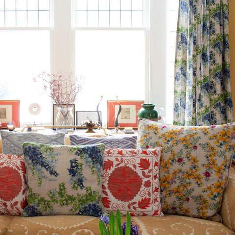 Floral illustrated throwpillow covers on a sofa with organic linen curtains in background.