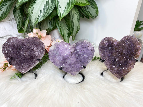 Carved purple amethyst heart crystals on a custom metal display stands. Super sparkly